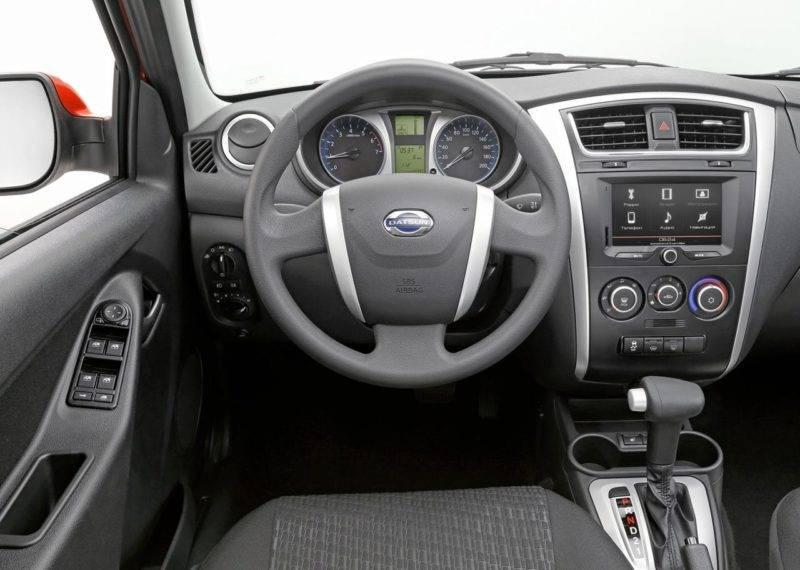 На трехспицевом руле расположена серебристая эмблема бренда Datsun.