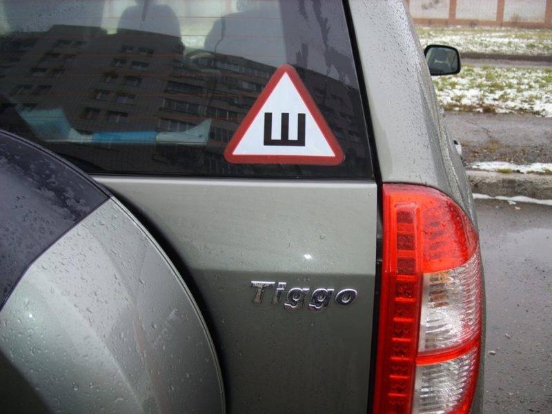 По закону знак должен быть на задней части автомобиля, при этом клеиться вершиной вверх. Наклейка размещается преимущественно на заднем стекле автомобиля.